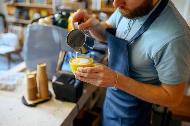 Barista maschio in grembiule versa schiuma nel caffè nella caffetteria. l'uomo fa un caffè espresso fresco nella caffetteria, cameriere al bancone del bar