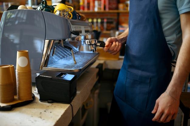 Barista maschio in grembiule prepara il caffè sulla macchina nella caffetteria