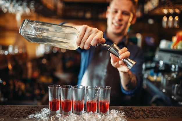 Il barman maschio in grembiule prepara cocktail alcolico