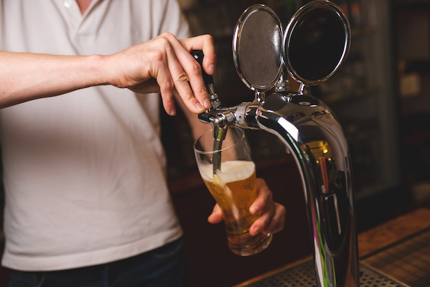 Un maschio barista versa un bicchiere di birra da un rubinetto