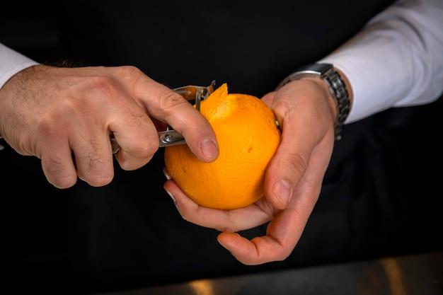 Barista maschio che sbuccia un'arancia