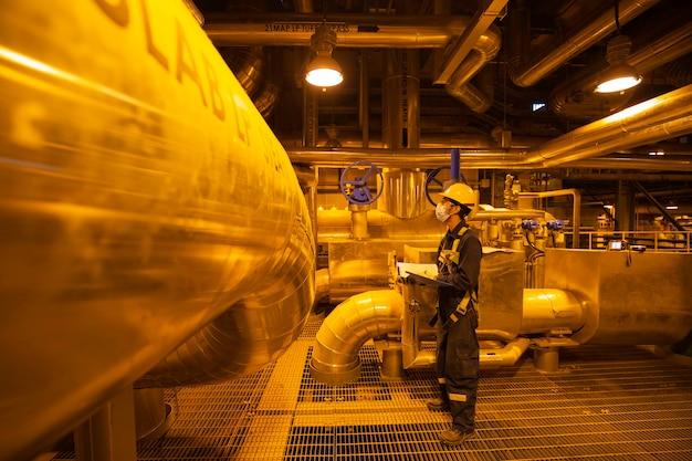 Maschio per essere ispezione visiva del lavoratore all'interno delle centrali elettriche della conduttura del serbatoio della valvola della sala di controllo