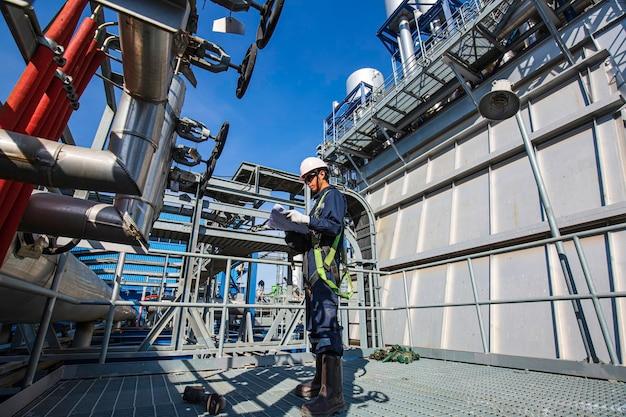 Maschio per essere operaio per l'ispezione visiva della conduttura e delle centrali elettriche della valvola