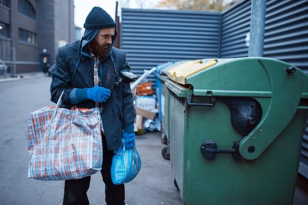 Mendicante barbuto maschio alla ricerca di cibo nel cestino sulla strada della città.
