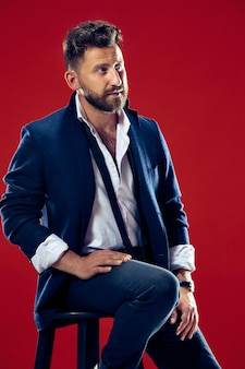 Ritratto di concetto di bellezza maschile di un giovane alla moda con un taglio di capelli alla moda che indossa un abito alla moda in posa su un muro rosso