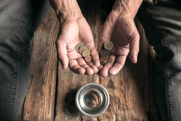 Mani di mendicanti maschi che cercano denaro, monete dalla gentilezza umana sul pavimento di legno in un percorso pubblico o in un passaggio pedonale. senzatetto poveri in città. problemi con le finanze, luogo di residenza.
