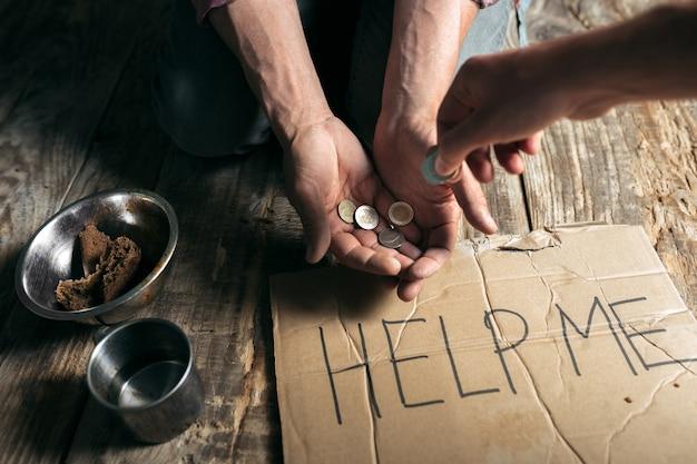 Mani di mendicante maschio in cerca di denaro con il segno aiutami dalla gentilezza umana sul pavimento di legno in un percorso pubblico o in un passaggio pedonale. senzatetto poveri in città. problemi con le finanze, luogo di residenza.