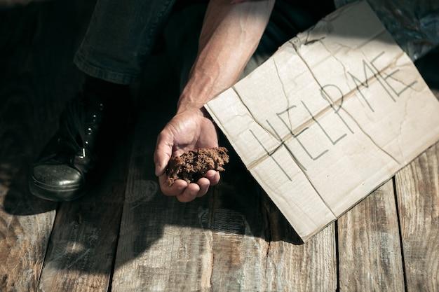 Il mendicante maschio passa alla ricerca di denaro sul pavimento di legno in un percorso pubblico