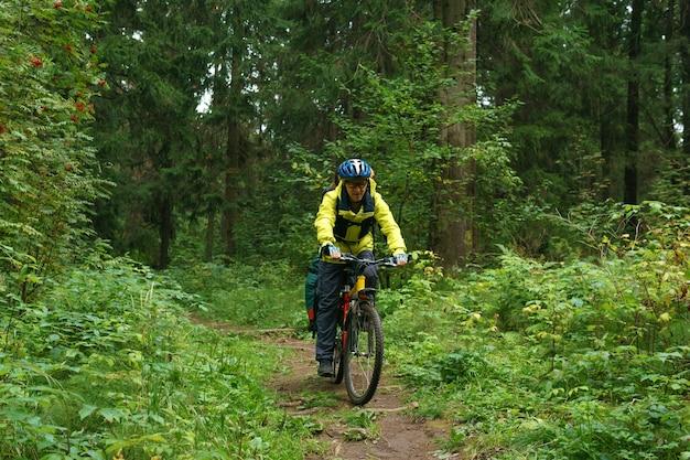 L'escursionista maschio della bicicletta guida su un sentiero nella foresta di montagna autunnale