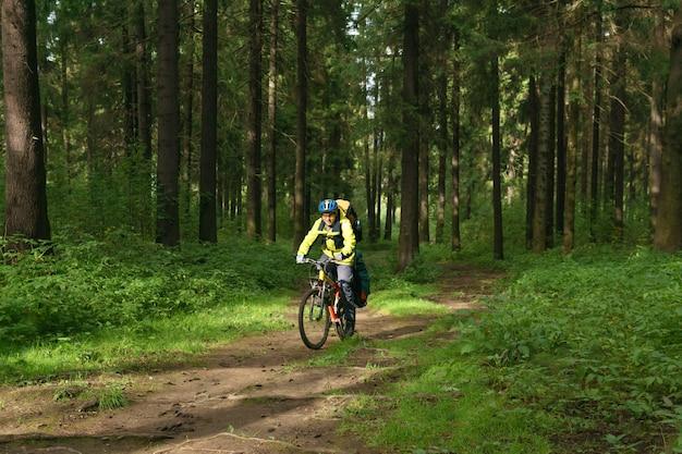 Il turista in bicicletta maschio percorre un ampio sentiero sterrato nella foresta autunnale