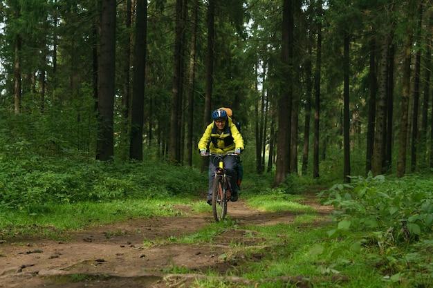 Il bikepacker maschio percorre un ampio sentiero sterrato nella foresta autunnale
