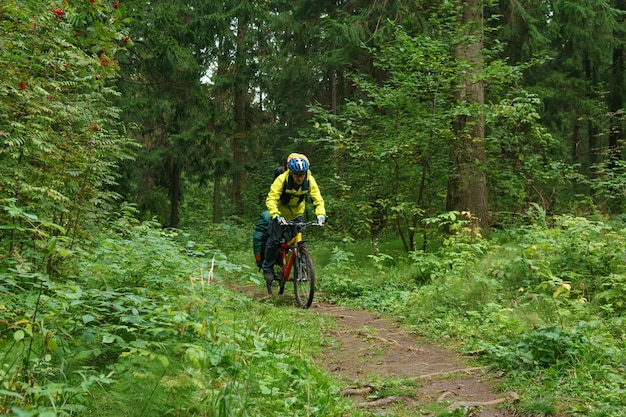 Bikepacker maschio cavalca su un sentiero nella foresta di montagna autunnale