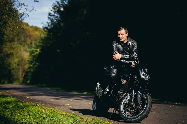 Motociclista maschio in una giacca di pelle nera che si siede su una moto sportiva nera su una strada forestale