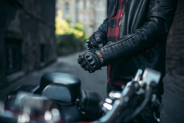 Motociclista maschio in giacca di pelle indossa i guanti prima di cavalcare il classico chopper