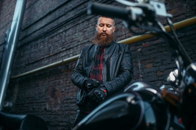 Motociclista maschio in giacca di pelle indossa i guanti