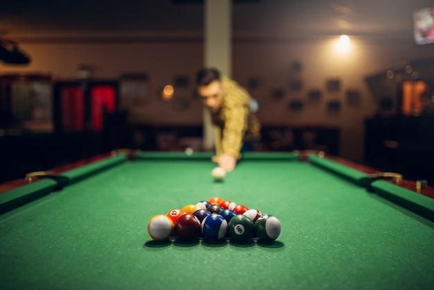 Giocatore di biliardo maschio con la stecca che mira al tavolo