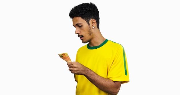 Atleta maschio nero con uniforme che tiene soldi brasiliani. sportivo isolato