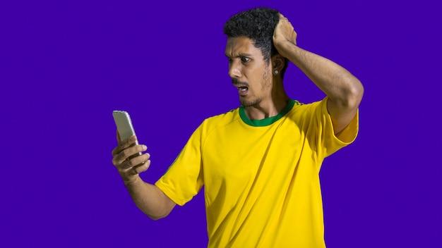 Atleta maschio nero con fotocamera mobile loking uniforme. sportivo isolato in uno sfondo di tessuto colorato. spazio per il testo.