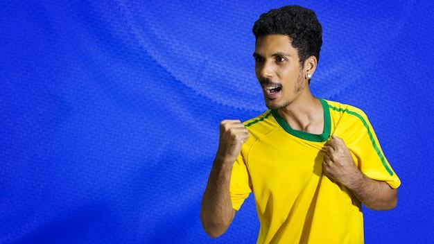 Atleta maschio nero con sorridente uniforme. sportivo isolato in uno sfondo di tessuto colorato. spazio per il testo.