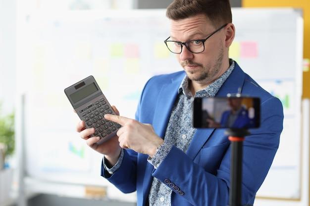 Il blogger maschio calcola i tassi di interesse redditizi sulla calcolatrice. formazione online sul concetto di deposito