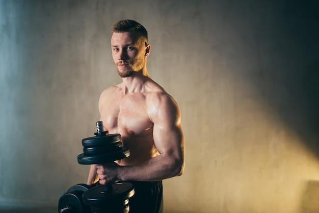 L'atleta biondo maschio solleva i manubri con la mano sulla foto dello studio del bicipite con le gocce di pioggia