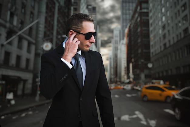 Guardia del corpo maschile in tuta e occhiali da sole parlando da auricolare di sicurezza, caos sulla strada cittadina