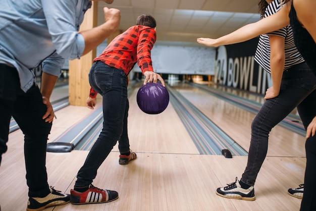 Il giocatore di bocce maschio sulla corsia si prepara a lanciare una palla, lanciando in azione, preparazione del colpo di colpo. squadre di bowling che giocano il gioco nel club, tempo libero attivo