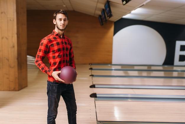 Giocatore di bocce maschio in piedi sulla corsia e tiene la palla in mano. il giocatore di bowling posa nel club, tempo libero attivo