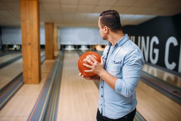 Giocatore di bocce maschio in piedi sulla corsia e pose con la palla