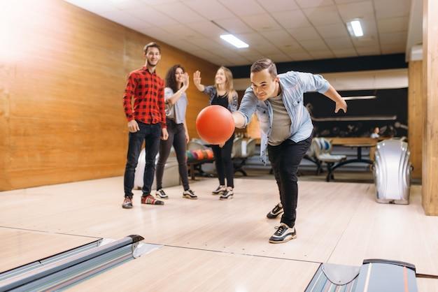 Il giocatore di bocce maschio lancia la palla sulla corsia. squadre di bowling che giocano il gioco nel club, tempo libero attivo