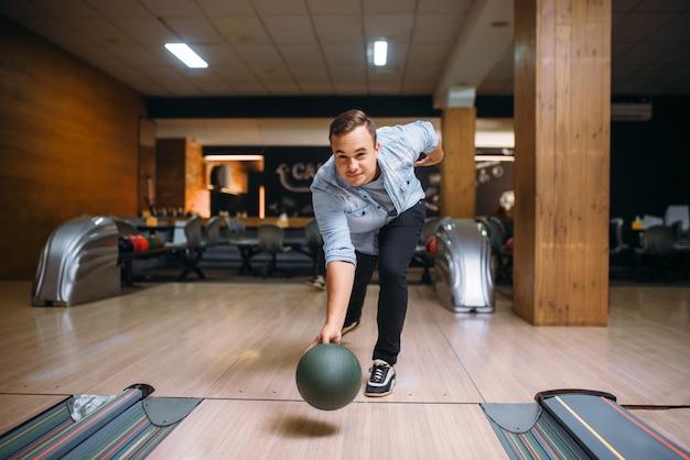 Giocatore di bocce maschio lancia la palla sulla corsia, vista frontale. giocatore di bowling, lancio in azione, classico gioco tenpin nel club, tempo libero attivo