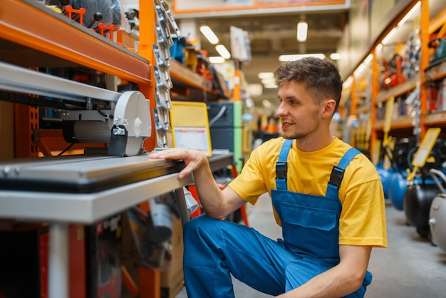 Costruttore maschio che sceglie la sega circolare allo scaffale nel negozio di ferramenta. costruttore in uniforme guarda le merci nel negozio di bricolage