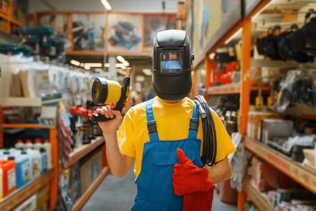 Generatore maschio che sceglie l'attrezzatura di saldatura allo scaffale nel negozio di ferramenta. costruttore in uniforme guarda le merci nel negozio di bricolage