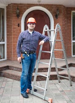 Costruttore maschio in casco in posa con scala di metallo contro l'ingresso della casa