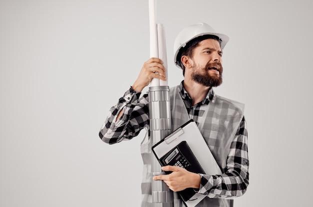 Il costruttore maschio con documenti e disegni progetta uno sfondo chiaro