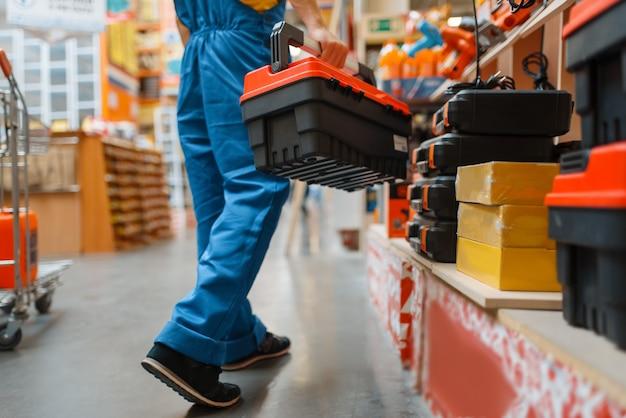 Costruttore maschio con cassetta degli attrezzi allo scaffale nel negozio di ferramenta. costruttore in uniforme guarda le merci nel negozio di bricolage