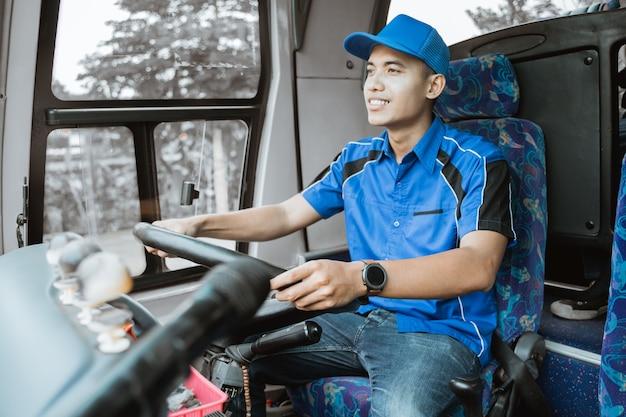 Un autista di autobus maschio in uniforme blu guida l'autobus