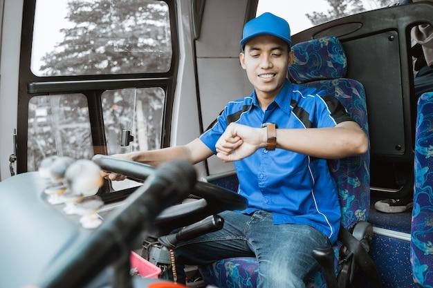 Un autista di autobus maschio in uniforme blu guarda il suo orologio mentre è seduto alla guida dell'autobus