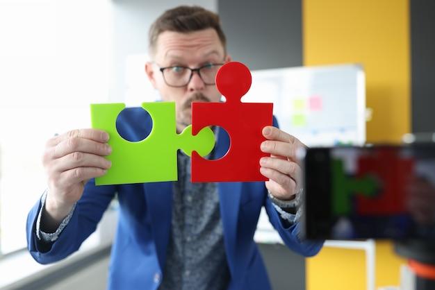 Business blogger maschio collega puzzle colorati alla ricerca di partner commerciali e soluzioni