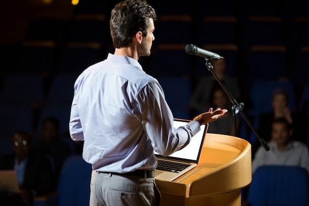 Uomo d'affari maschio che dà un discorso al centro congressi