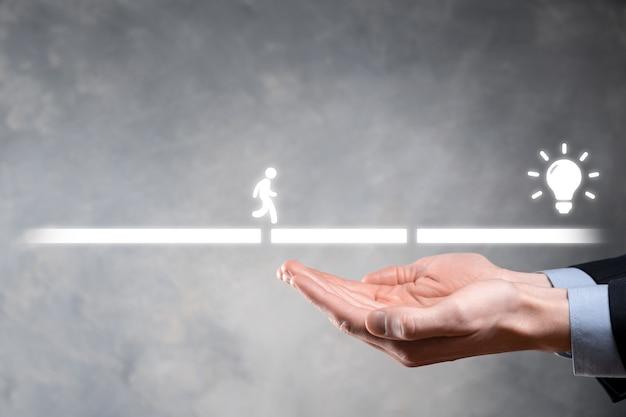 La mano maschio dell'uomo di affari tiene un blocco di collegamento tra due serie di ponti stradali per un uomo che si staglia per camminare icona dell'idea.