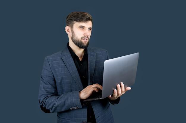 Un uomo d'affari in abito blu tiene in mano un laptop