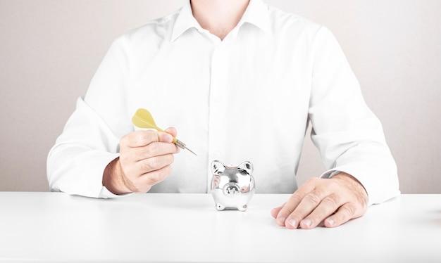 L'uomo d'affari maschio colpisce l'obiettivo con i dardi. concetto di aspirazione dei dadi con salvadanaio
