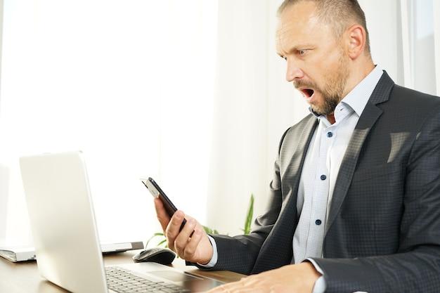 Un uomo d'affari maschio legge le notizie sul suo smartphone ed è scioccato e sorpreso