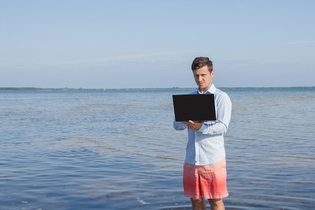 Uomo d'affari maschio con camicia elegante e costume da bagno con un computer portatile in mare