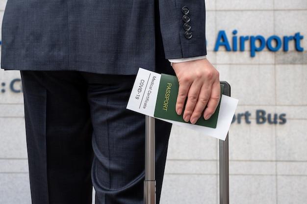 Un uomo d'affari maschio con certificato sanitario e passaporto per il covid-19. post-covid-19 concetto di business.