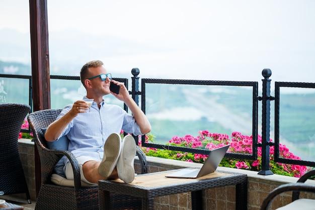 Uomo d'affari maschio che lavora su un laptop in vacanza con una bellissima vista panoramica. manager di successo che beve caffè e parla al telefono con il caffè durante il viaggio