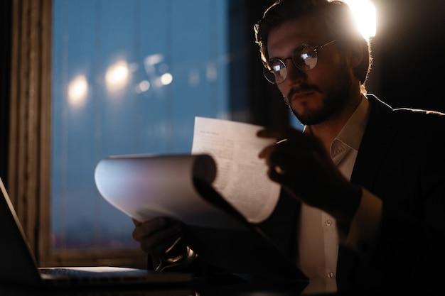 L'uomo d'affari maschio lavora con rapporti aziendali e grafici finanziari. scartoffie a tarda notte.