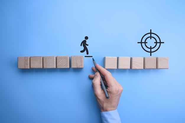 Mano dell'uomo maschio di bussinnes che disegna una linea di collegamento tra due serie di blocchi di legno affinchè un uomo staglia attraversi a piedi. concettuale di lavoro di squadra e supporto.