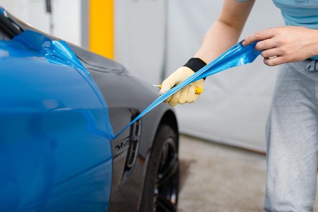 Le mani di wrapper per auto maschili installano un foglio o un film in vinile protettivo sulla portiera del veicolo. il lavoratore fa i dettagli automatici. protezione della vernice dell'auto, messa a punto professionale
